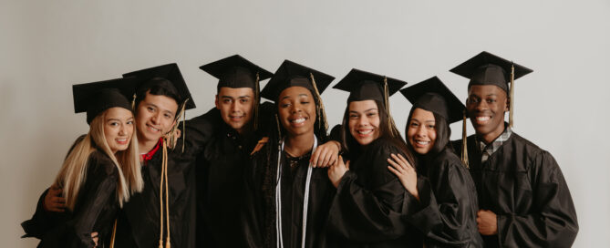 Group of youth Banyan Community members wearing graduation gowns smiling with arms around each other
