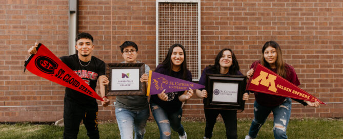 Five high school youth holding college banners